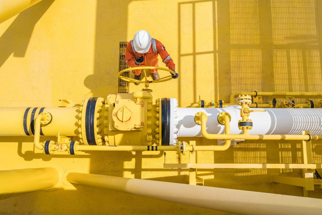 Fotografia mostra homem trabalhador, visto de cima, operando manilha de duto de transporte de gás natural