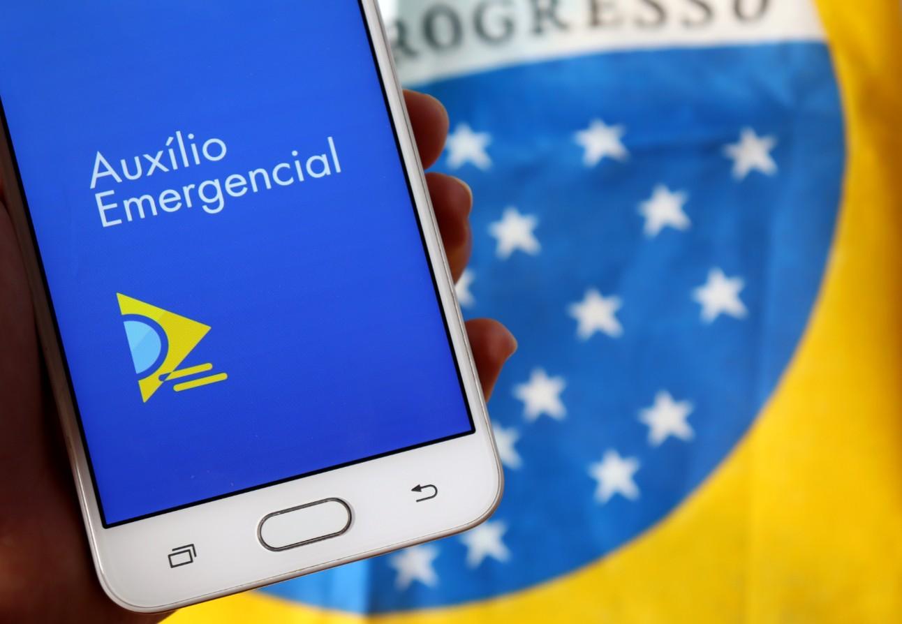 Imagem de um celular mostrando o aplicativo do Auxílio Emergencial, com a bandeira do Brasil ao fundo