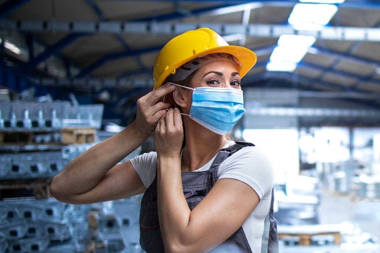 Operária feminina de uniforme e capacete de segurança, colocando uma máscara facial na planta de produção industrial. Pessoas que trabalharam durante a pandemia Covid-19
