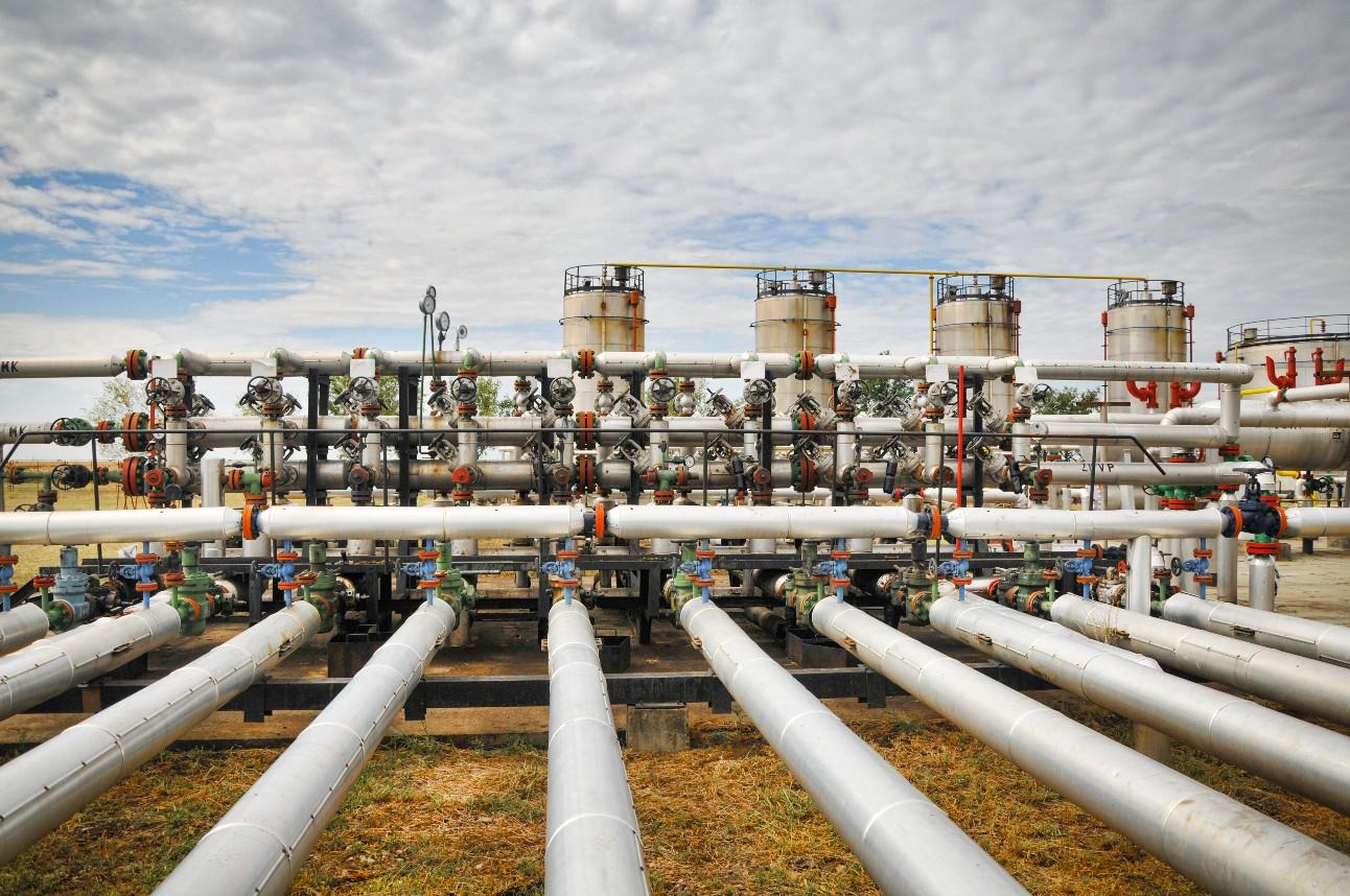 Foto mostra homem branco de costas, fazendo medições em estação de tratamento de gás natural