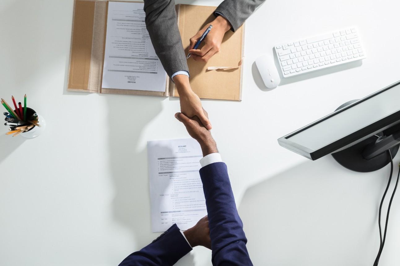 Empresário apertando a mão de uma pessoa interessada em uma vaga de emprego