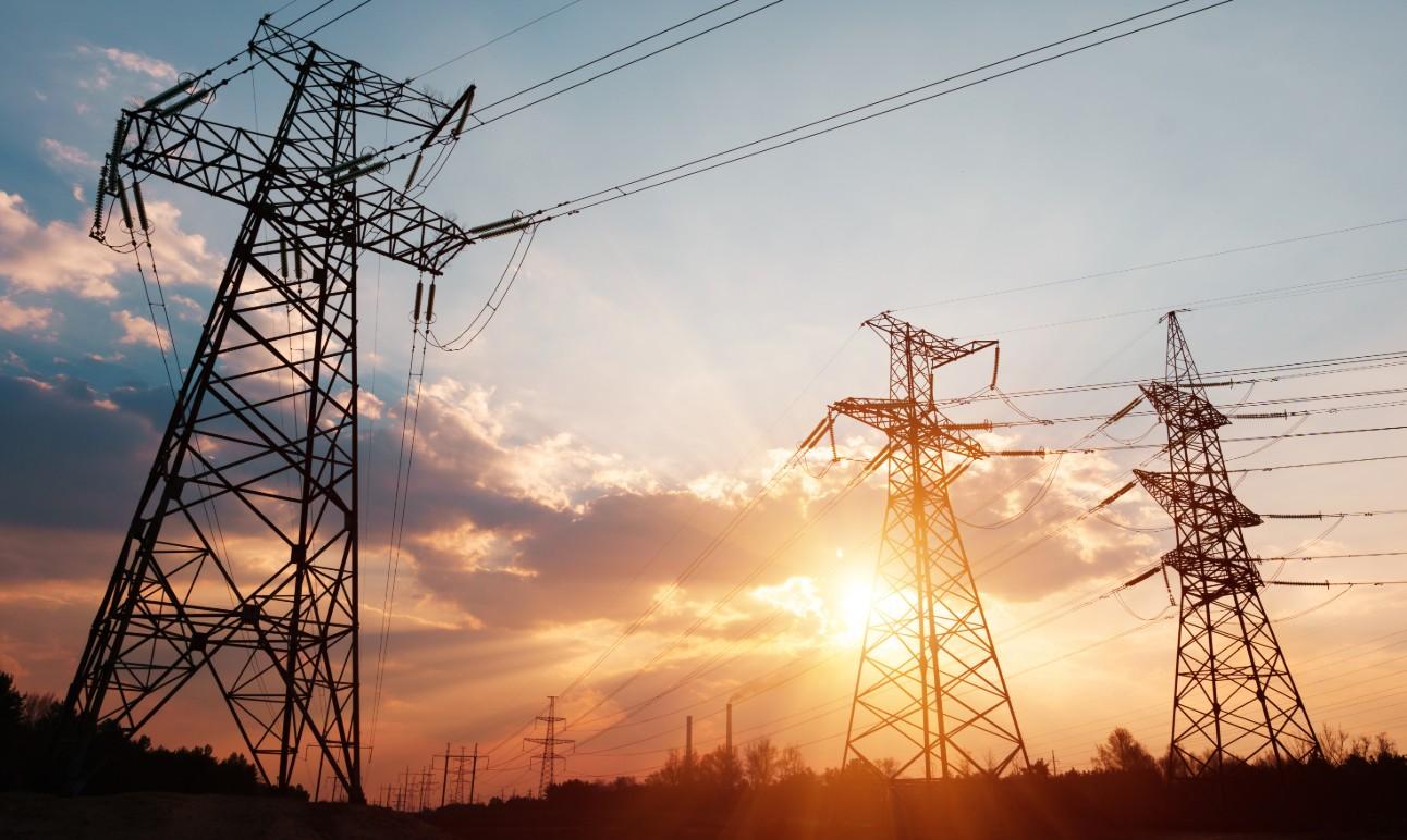 Imagem de torres de eletricidade no por do sol.
