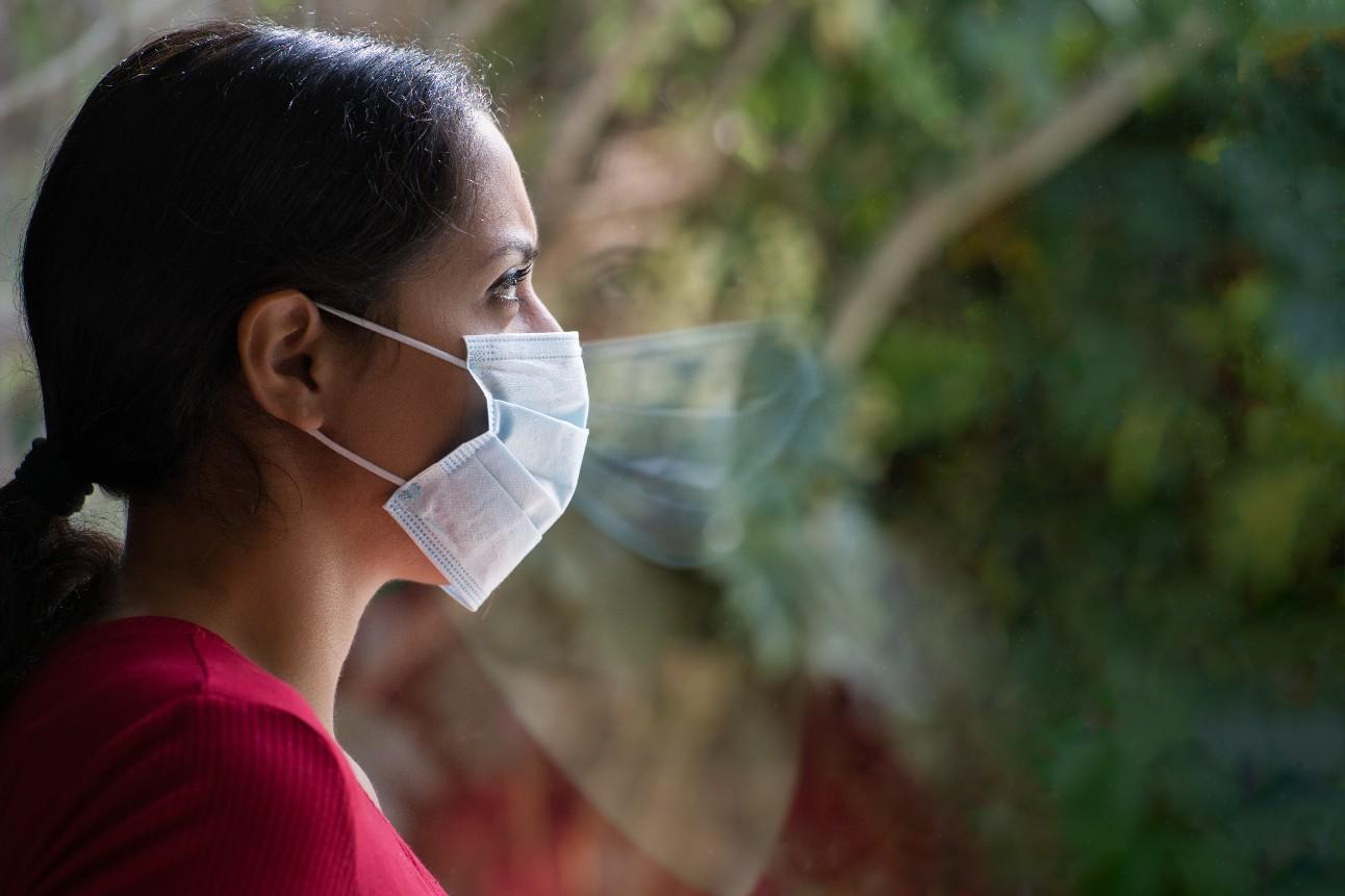 Jovem mulher triste usando uma máscara facial, olhando pela janela com seu reflexo no vidro