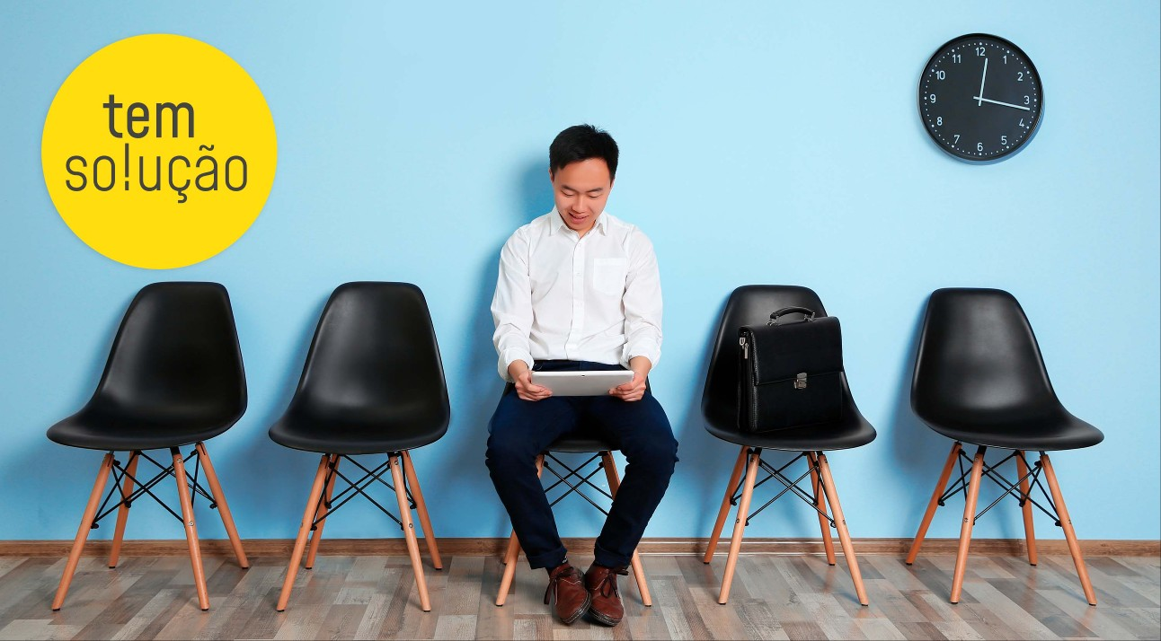 homem asiático, vestido com uma camisa branca e calças pretas, sentado em uma cadeira enquanto lê seu currículo