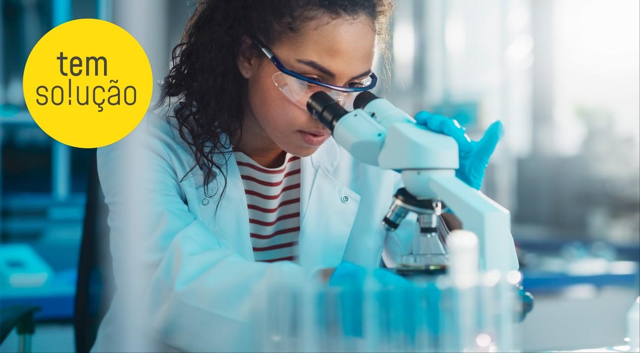 mulher negra usando jaleco examina algo em laboratório