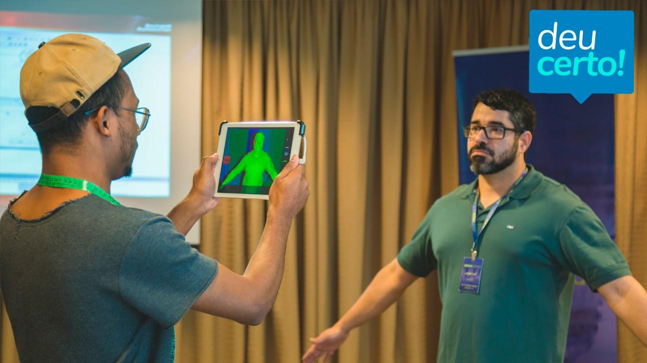 Fotografia mostra dois homens: um, de boné, com um tablet fazendo o escanemento do modelo