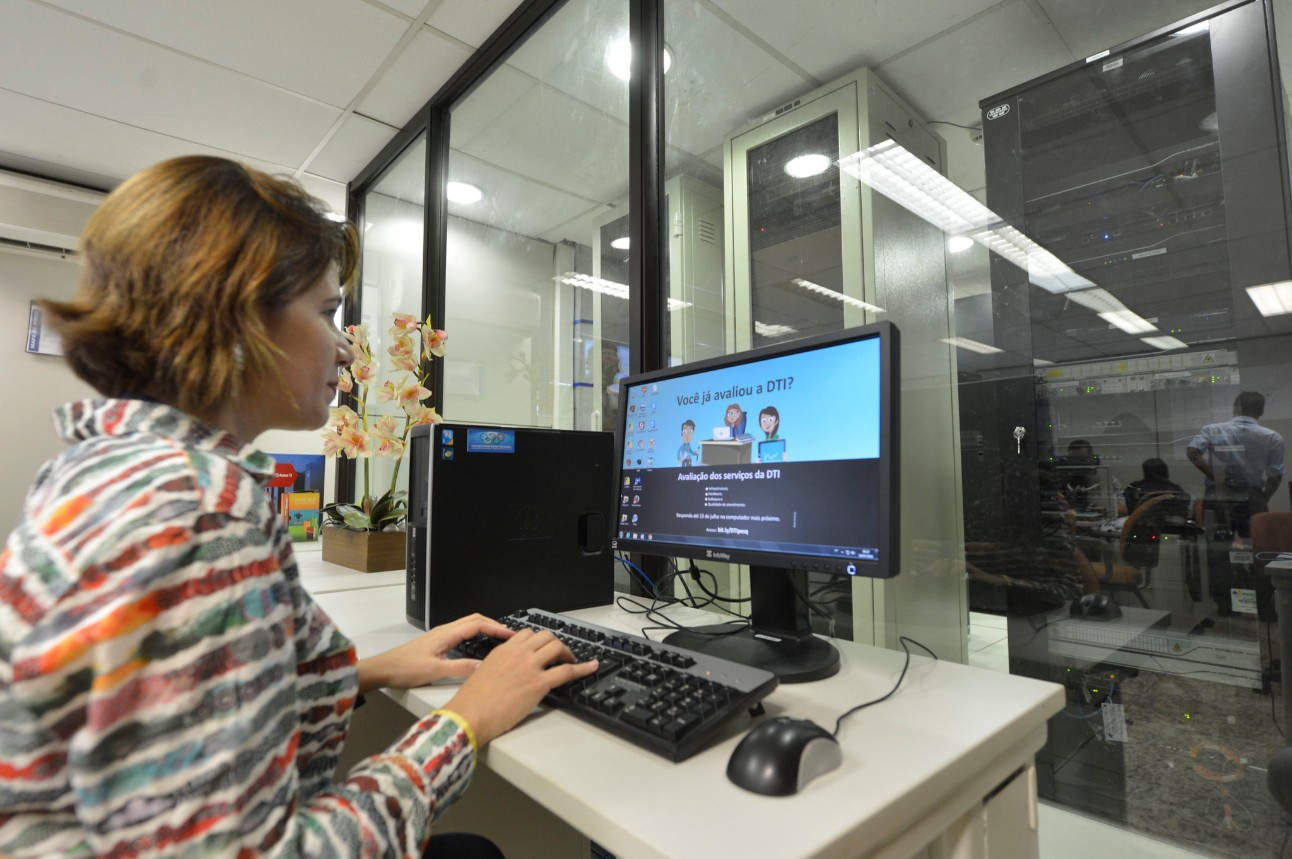 Mulher sentada em um ambiente de escritório, olhando para tela do computador e digitando no teclado