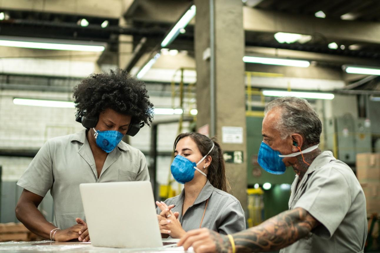 Trabalhadores da indústria em medidas de controle da Covid, com uso de máscaras