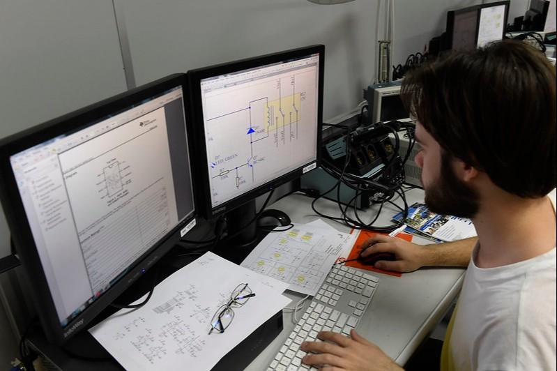 Jovem concentrado e olhando para duas telas de computadores durante treinamento digital